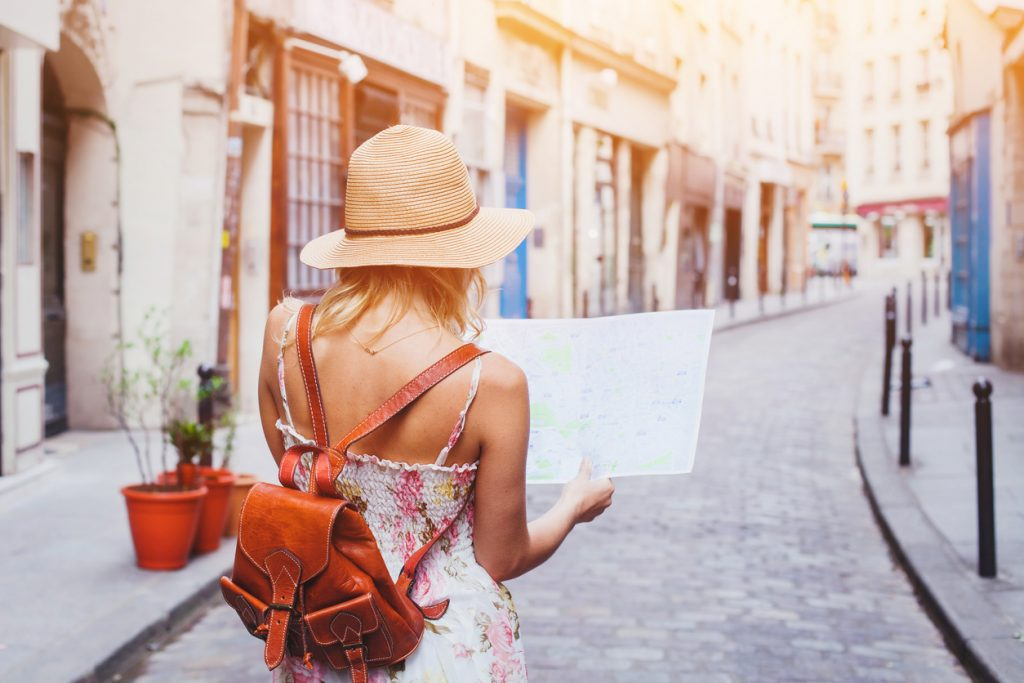 woman tourist looking at a map on a street
